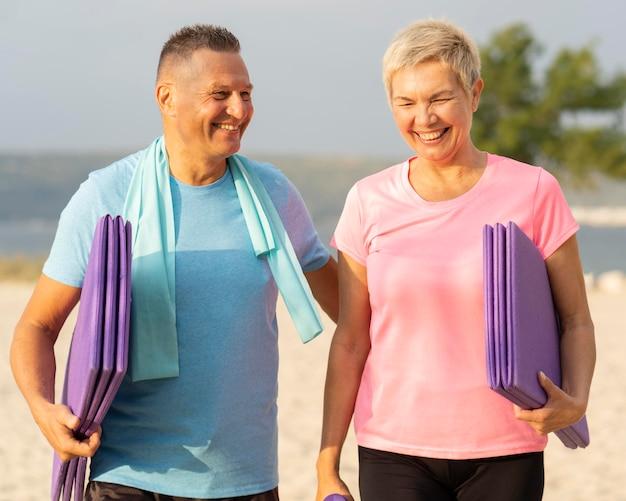 Casal sorridente de idosos com equipamento de ginástica na praia