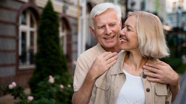 Casal sorridente de idosos posando juntos enquanto caminhavam pela cidade