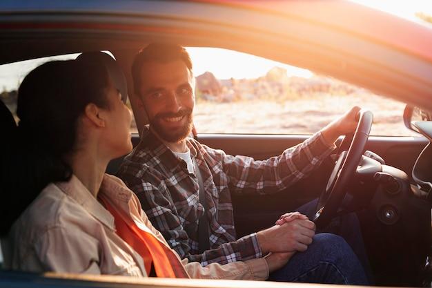 Casal sorridente de lado viajando de carro