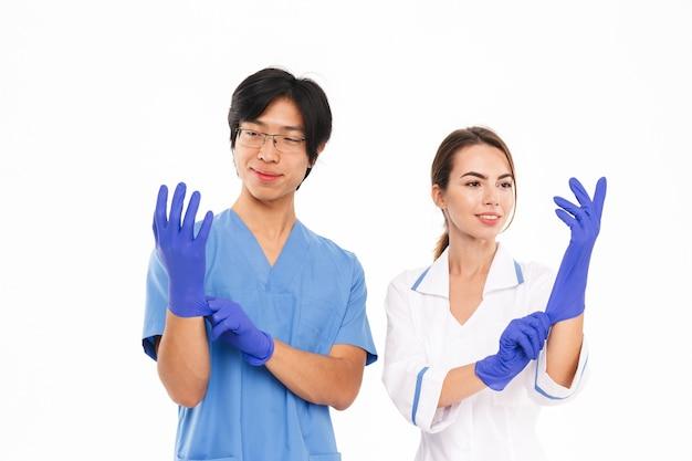 Casal sorridente de médicos usando uniforme e luvas de borracha, isolado na parede branca