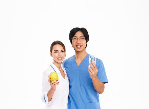 Casal sorridente de médicos usando uniforme em pé, isolado na parede branca, mostrando maçã verde e um copo d'água
