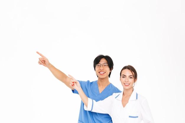 Casal sorridente de médicos vestindo uniforme em pé, isolado na parede branca, apontando para o espaço da cópia