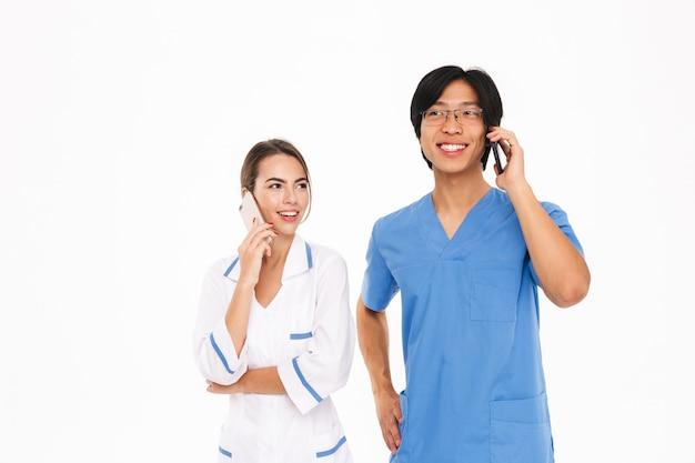 Casal sorridente de médicos vestindo uniforme em pé, isolado na parede branca, falando no celular