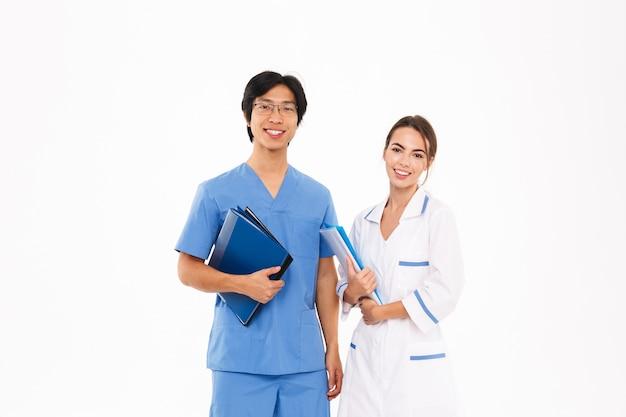 Casal sorridente de médicos vestindo uniforme em pé, isolado na parede branca, segurando pastas
