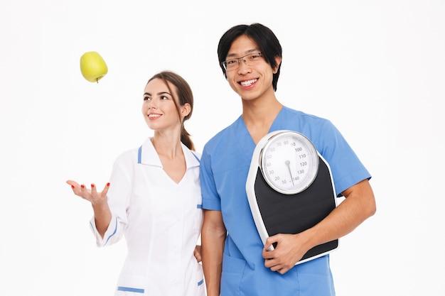 Casal sorridente de médicos vestindo uniforme em pé, isolado na parede branca, segurando uma balança e maçã verde