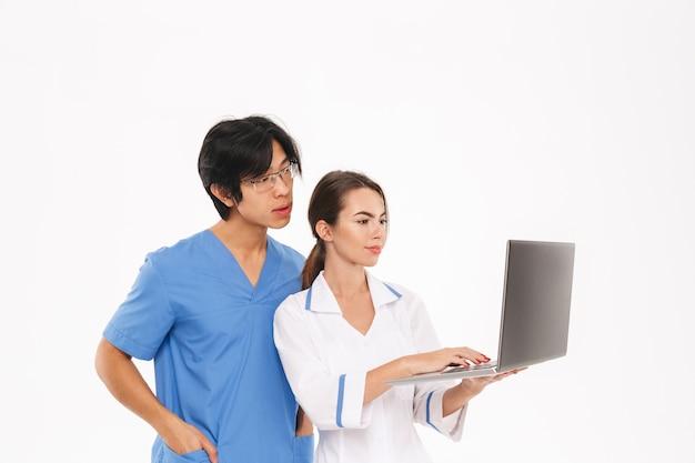 Casal sorridente de médicos vestindo uniforme em pé, isolado na parede branca, trabalhando em um computador laptop