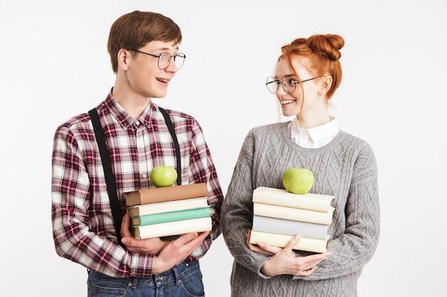 Casal sorridente de nerds escolares segurando uma pilha de livros
