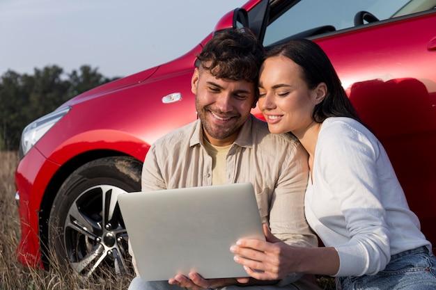 Casal sorridente de tiro médio com laptop