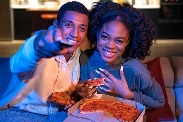 Casal sorridente de tiro médio com pizza