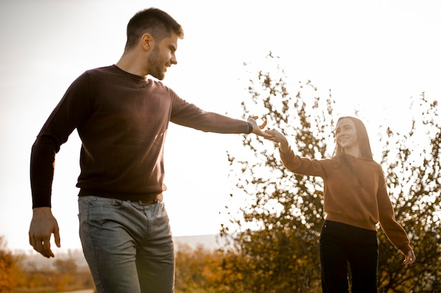 Casal sorridente de tiro médio de mãos dadas