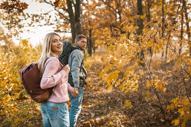 Casal sorridente de turistas andando por um caminho de floresta de mãos dadas e olhando para a câmera