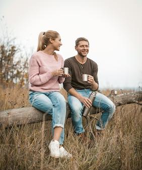 Casal sorridente de turistas bebe chá e conversa enquanto está sentado na árvore caída entre uma natureza outono ao ar livre