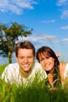 Casal sorridente, deitado em um campo ensolarado