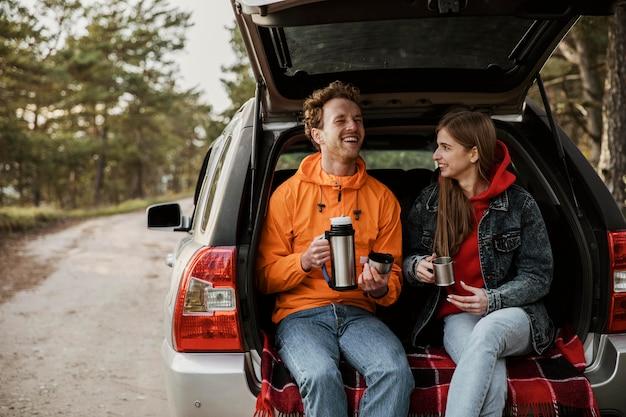 Casal sorridente desfrutando de uma bebida quente no porta-malas do carro