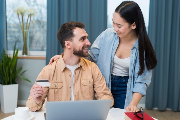 Casal sorridente, desfrutando de uma sessão de compras on-line