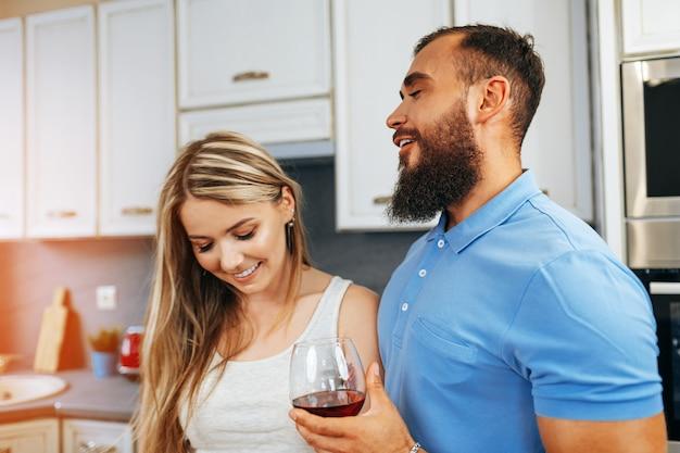 Casal sorridente e alegre cozinhando e bebendo vinho na cozinha de casa