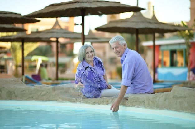 Casal sorridente e divertido de férias perto da piscina