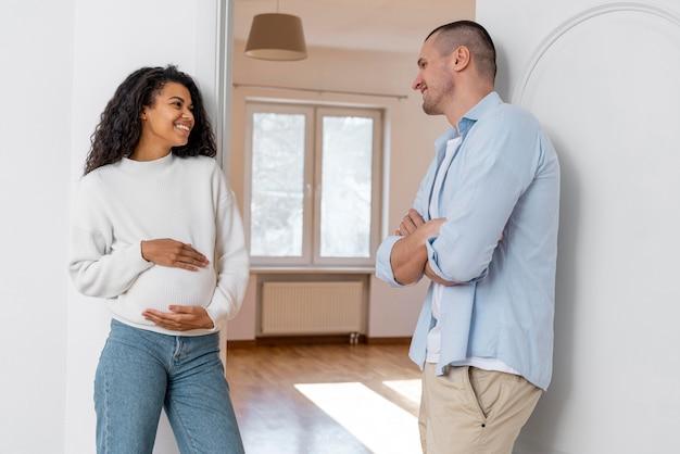 Casal sorridente e grávida em pé do lado de fora da casa nova