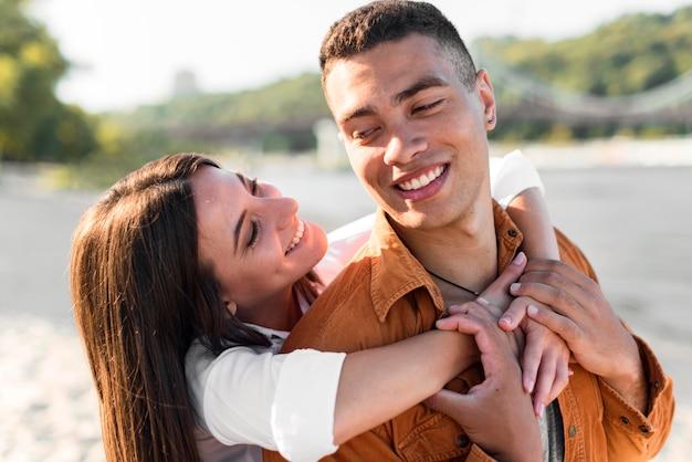 Casal sorridente e romântico passando um tempo na praia juntos