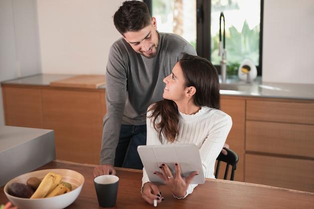 Casal sorridente em casa na cozinha