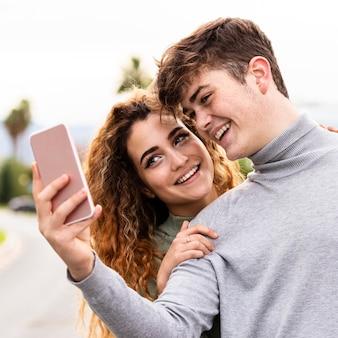 Casal sorridente em close fazendo uma selfie
