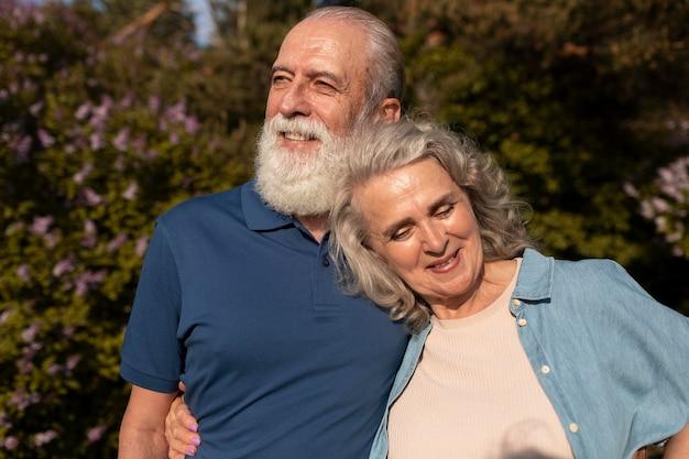Casal sorridente em foto média ao ar livre