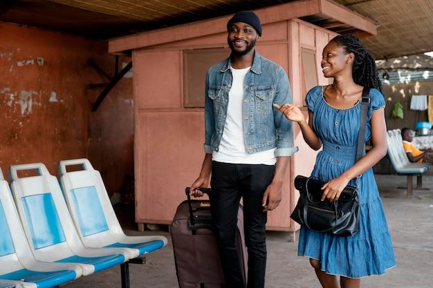 Casal sorridente em foto média com bolsas