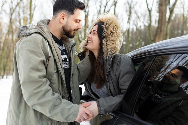 Casal sorridente em foto média com carro