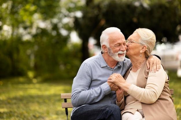 Casal sorridente em foto média do lado de fora