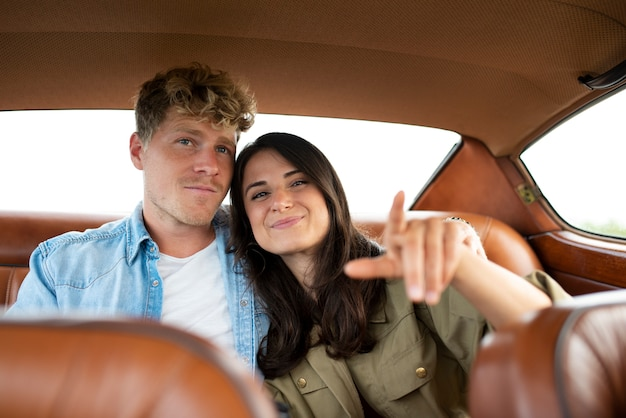 Casal sorridente em foto média no carro