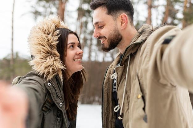 Casal sorridente em foto média tirando uma selfie