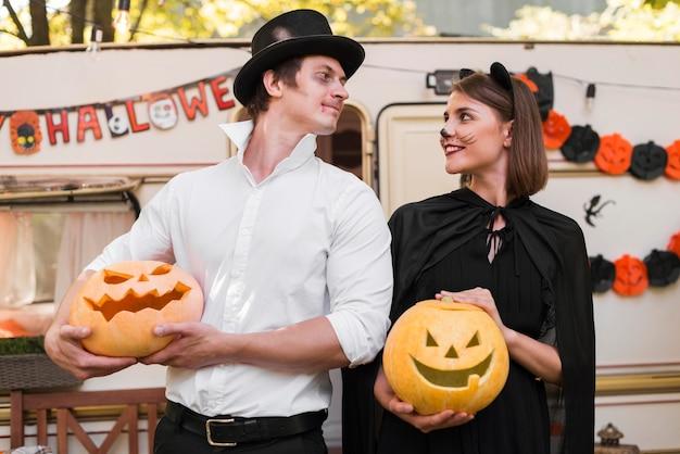 Casal sorridente em foto média usando fantasias
