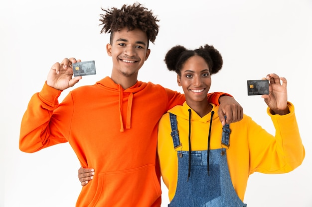Casal sorridente em pé juntos segurando cartões de crédito, isolados sobre uma parede branca
