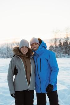 Casal sorridente em pé na paisagem de neve