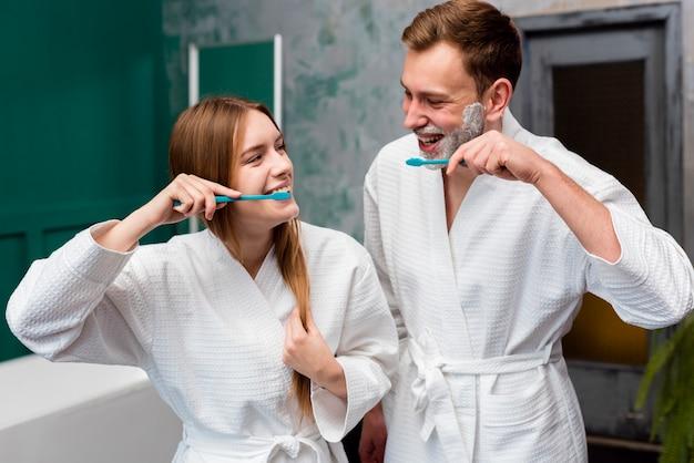 Casal sorridente em roupões de banho, escovar os dentes