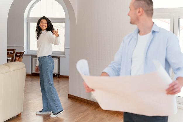 Casal sorridente em sua nova casa fazendo planos de casa