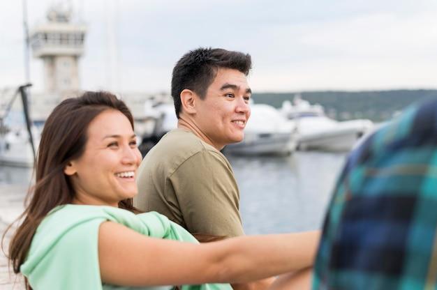 Casal sorridente encontrando seus amigos ao ar livre