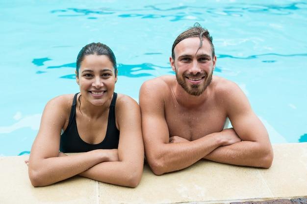 Casal sorridente encostado na piscina