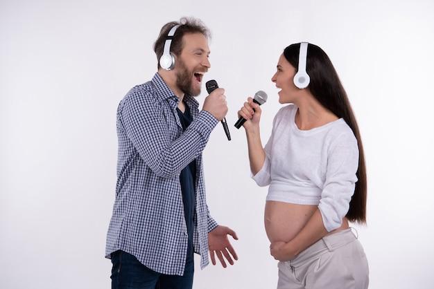 Casal sorridente está usando fones de ouvido. família jovem.