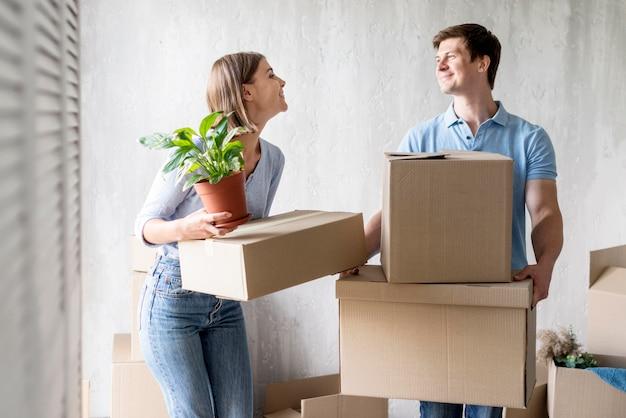 Casal sorridente fazendo as malas para mudar de casa