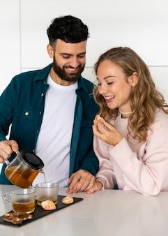 Casal sorridente fazendo chá em casa juntos