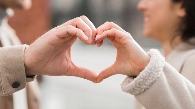 Casal sorridente fazendo formato de coração com as mãos