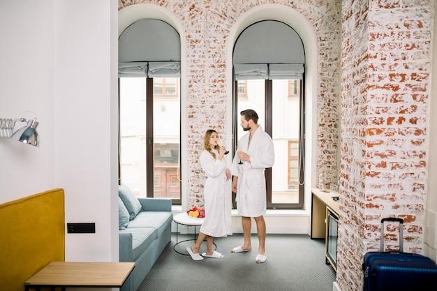 Casal sorridente feliz bebendo champanhe em pé no quarto ou apartamento de hotel. dia dos namorados ou aniversário. quarto em casa ou no hotel.