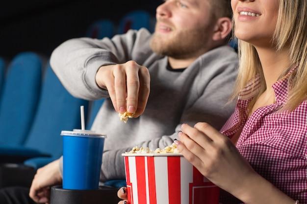 Casal sorridente feliz comendo pipoca no cinema