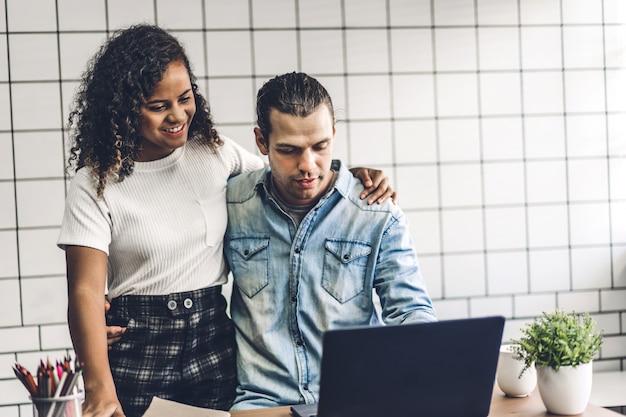Casal sorridente feliz trabalhando juntos com o computador portátil. casal de negócios criativos planejamento e brainstorm na sala de estar em casa