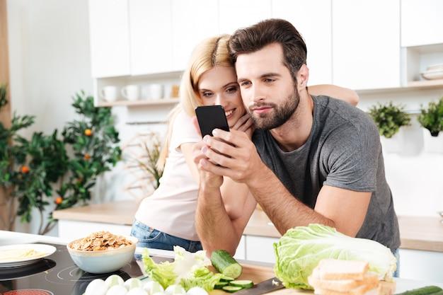 Casal sorridente feliz usando telefone celular para encontrar uma receita