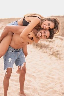 Casal sorridente na praia se divertindo