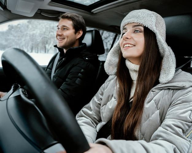Casal sorridente no carro durante uma viagem