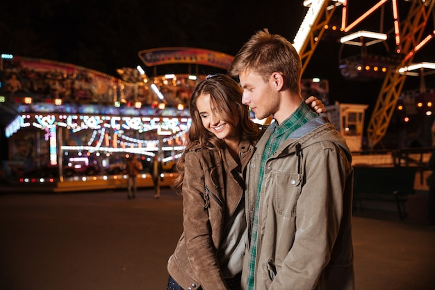 Casal sorridente no parque de diversões.