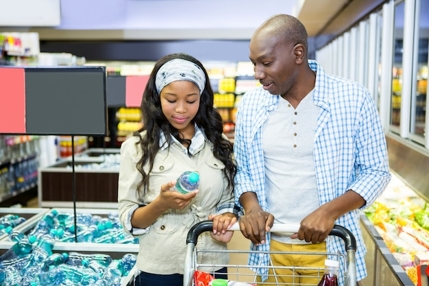 Casal sorridente, olhando para a garrafa de água na seção de compras